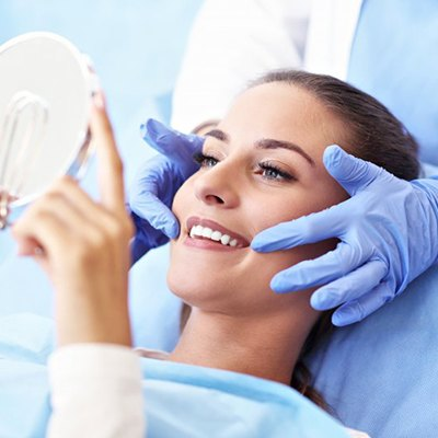 woman admiring her smile after getting dental bonding in Springfield